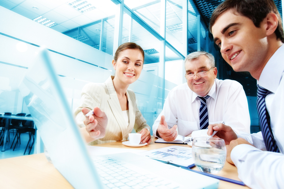 A business team of three sitting in office and planning work